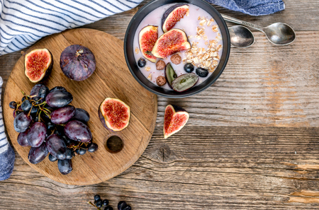 An useful dessert - yogurt, muesli and figs with grapes top view