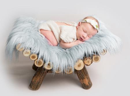 Newborn baby girl sleeps on small wooden crib. Stock Photo