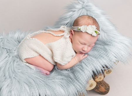 Newborn baby girl sleeps on small wooden crib. Stock Photo
