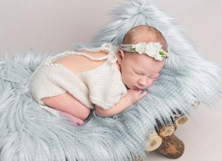 Newborn baby girl sleeps on small wooden crib. Stockfoto
