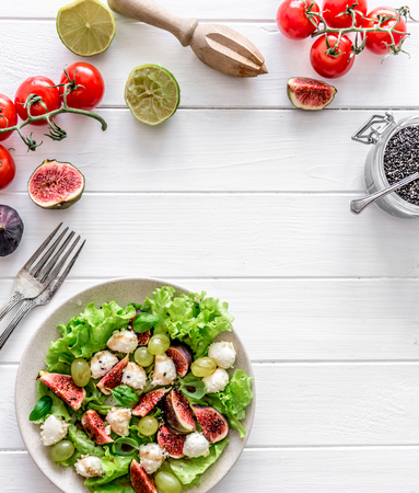 Salad with figs, mozzarella and grapes on a white wooden background. Archivio Fotografico