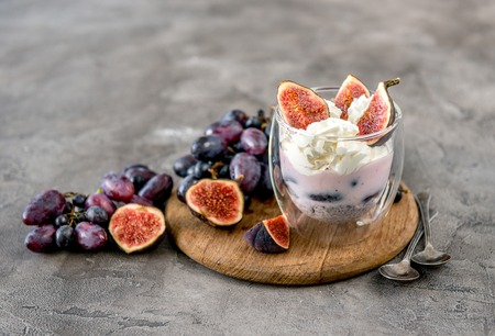 An useful dessert - yogurt, muesli and figs with grapes Фото со стока