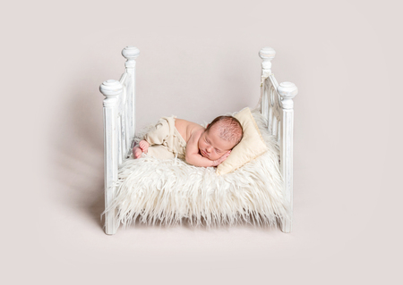 Lovely newborn baby on small crib