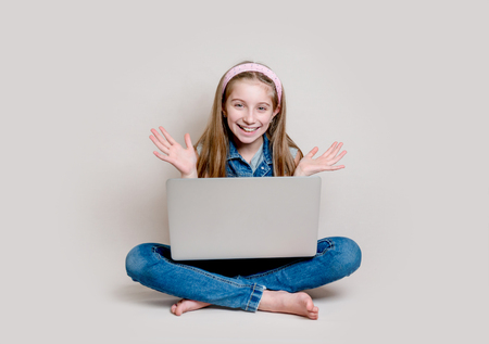 Cheerful little girl sitting on the floor with laptop Stock Photo