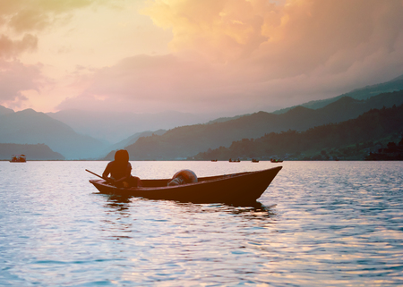 fisherman in a boat on the lake in Pokhara at sunset