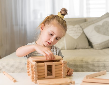 Portrait of little girl with house model.