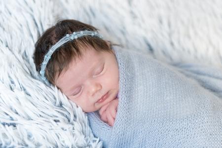 Newborn girl in blue wrap