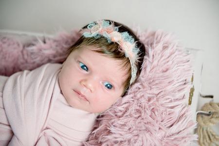 Beautiful newborn baby girl with wreath