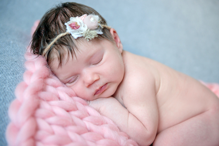 Tender newborn sleeping with wreath on head