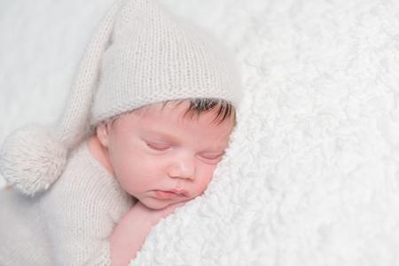Newborn sleeping tenderly on soft bed Stock Photo