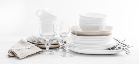 Stack of mixed white dishes and crystal glasses