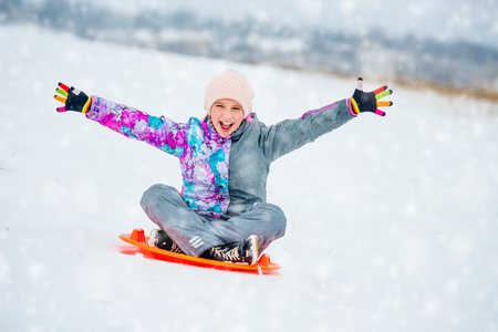 Girl sliding down the hill on saucer sled 版權商用圖片