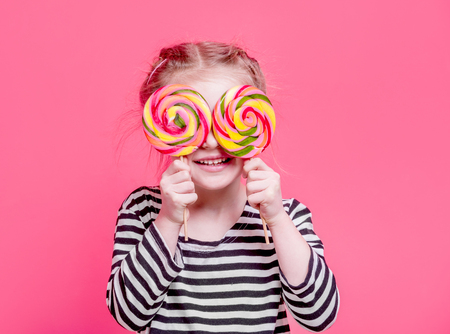Kid girl with lollypops in front her eyes