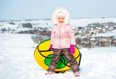 Little cheerful girl with snow tube