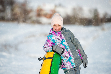Girl with inflatable snow sled on downhill at winter