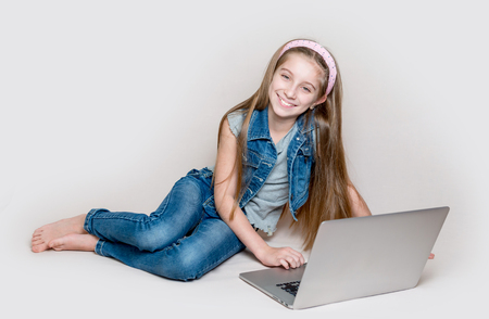 Litlle girl lying on floor with laptop