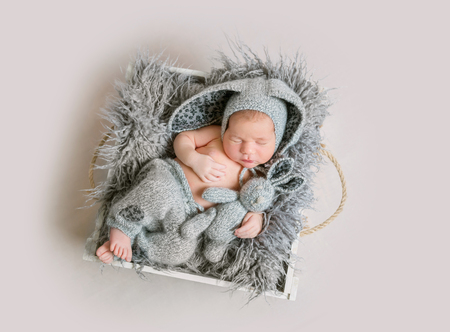 Funny newborn boy in grey bunny bonnet and grey knitted pants sleeping and holding bunny toy in his hand on wooden box with fluffy banket. Top view. Reklamní fotografie