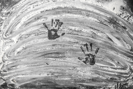 White baking flour on black slate background with traces of childs hands top view Stock Photo