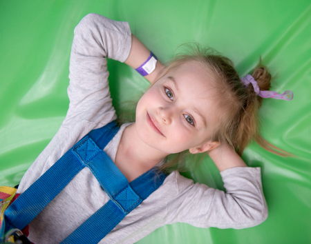 Little girl laying on green gym mat