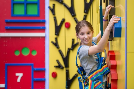 Little girl hanging on holds on climbing wall