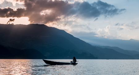 fisherman in a boat on the lake in Pokhara Stock Photo