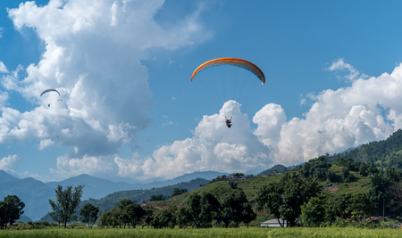 landing with parachute after paragliding in Nepal