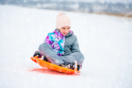 Girl sliding down the hill on saucer sled Banque d'images - 96764654
