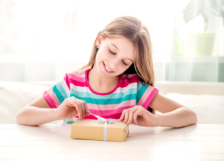 Smiling girl unwrapping present box