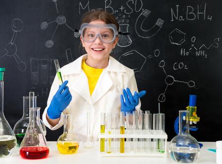 液体で実験をする白いガウンの女子高生