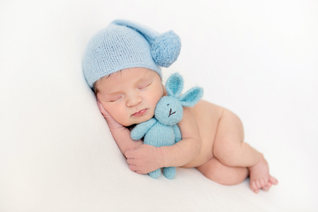 Lovely newborn baby boy hugging his plush toy