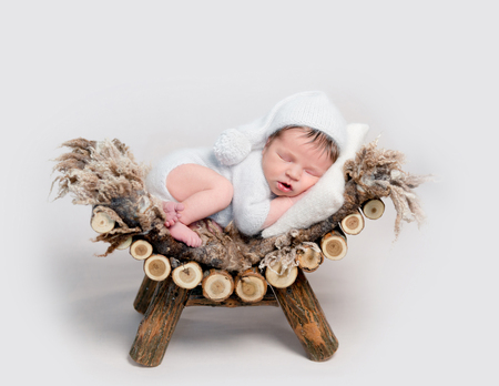 Newborn baby asleep on belly curled up on crib