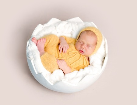 Sleeping newborn baby boy curled up on round basket, top view Stock Photo