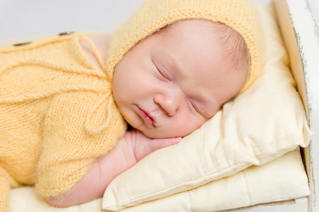 Baby dressed in knitted yellow costume sleeping on crib Stock Photo