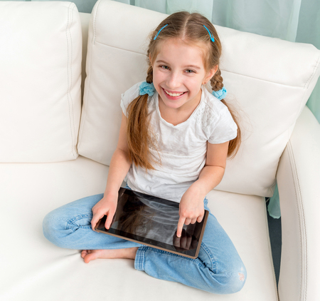 cheerful little girl with tablet on her legs looking at camera