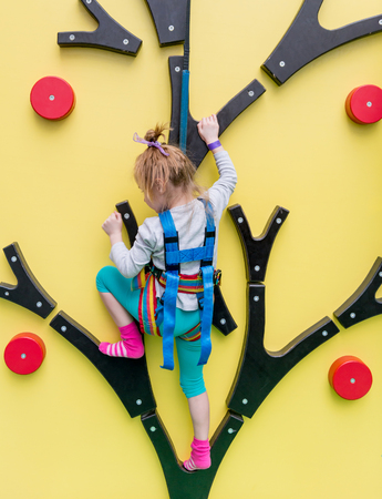 Little girl in insurance trains on climbing wall 스톡 콘텐츠