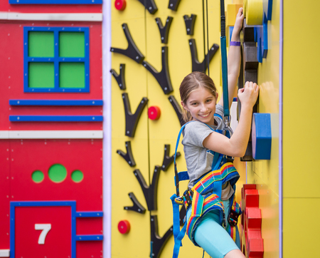 Little girl hanging on holds on climbing wall 스톡 콘텐츠 - 98703209