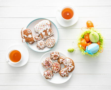 Easter cookies and colorful eggs on white wooden background