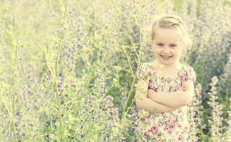 little girl with her arms folded, spring field Banque d'images - 98703317