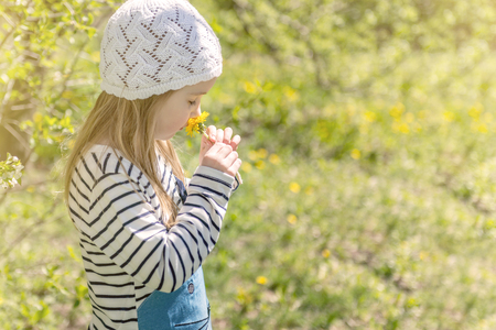 Lovely little girl smelling flowers in garden
