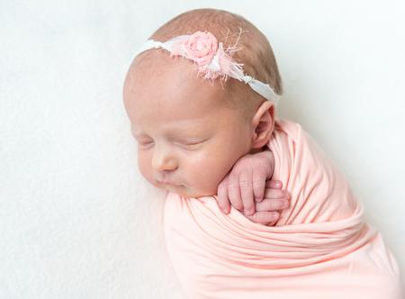 Sleeping newboen baby in a pink wrap
