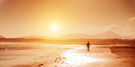 Surfer on the ocean beach at sunset on  Canary Islands