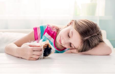 Girl stroking fluffy guinea pig