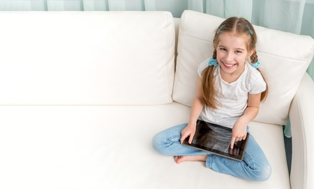 cheerful little girl with tablet on her legs looking at camera Stock Photo