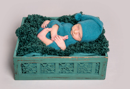 Newborn baby lying in wooden crate