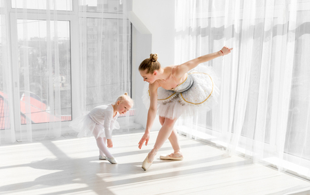 Young gorgeous ballerina with her little daughter dancing in studio 写真素材