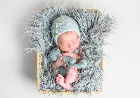 Newborn baby peacefully sleeping in a basket Stock Photo