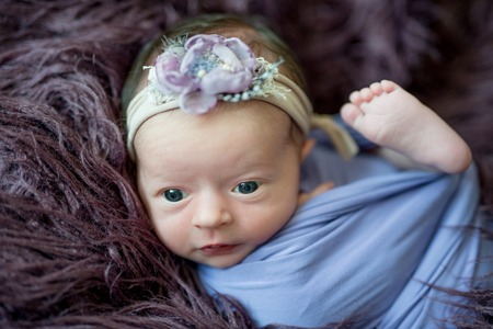 Newborn girl with headband wrapped in blue swaddle