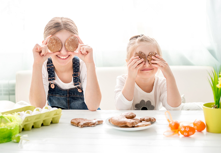 Happy little girls holding Easter cookies in front of their eyes