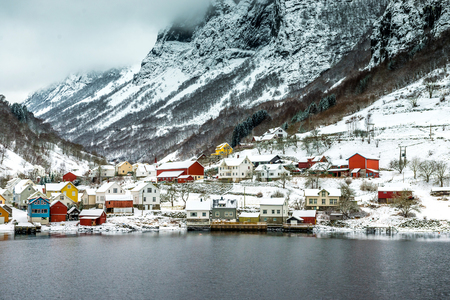 journey through fjord. red house on a background of the rocky mountains Stock Photo