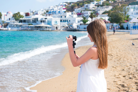 Little girl on the beach with GoPro camera making photo Stock Photo